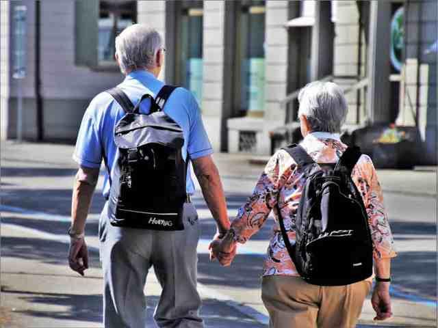 elderly couple holding hands image