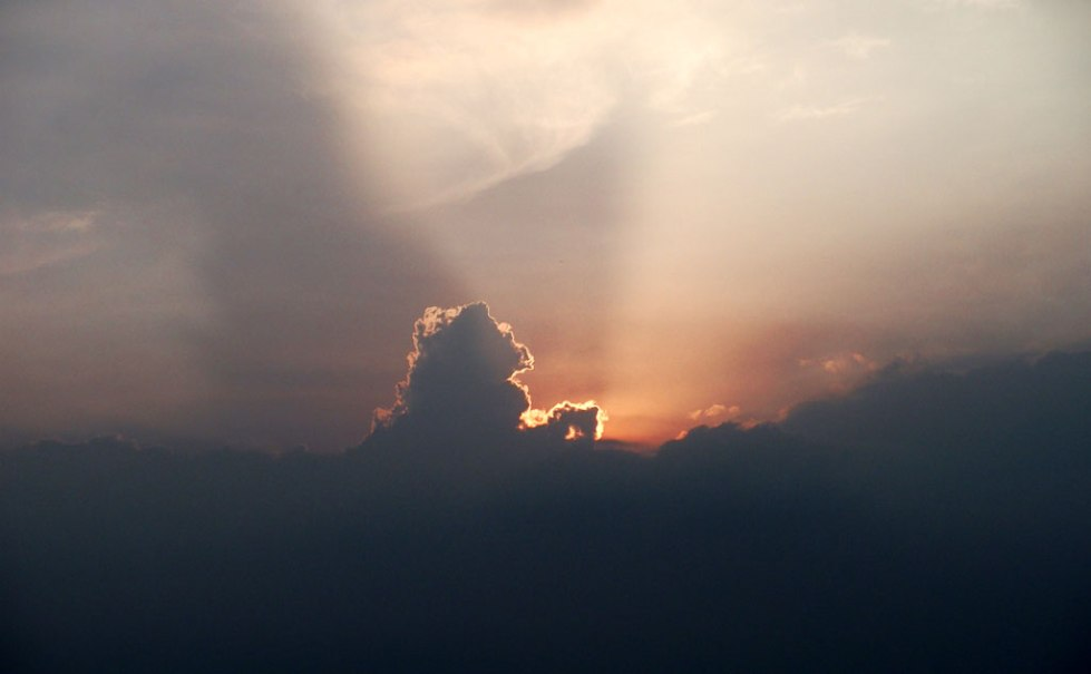 sun rays throws light from behind clouds which is shaped like a horse.