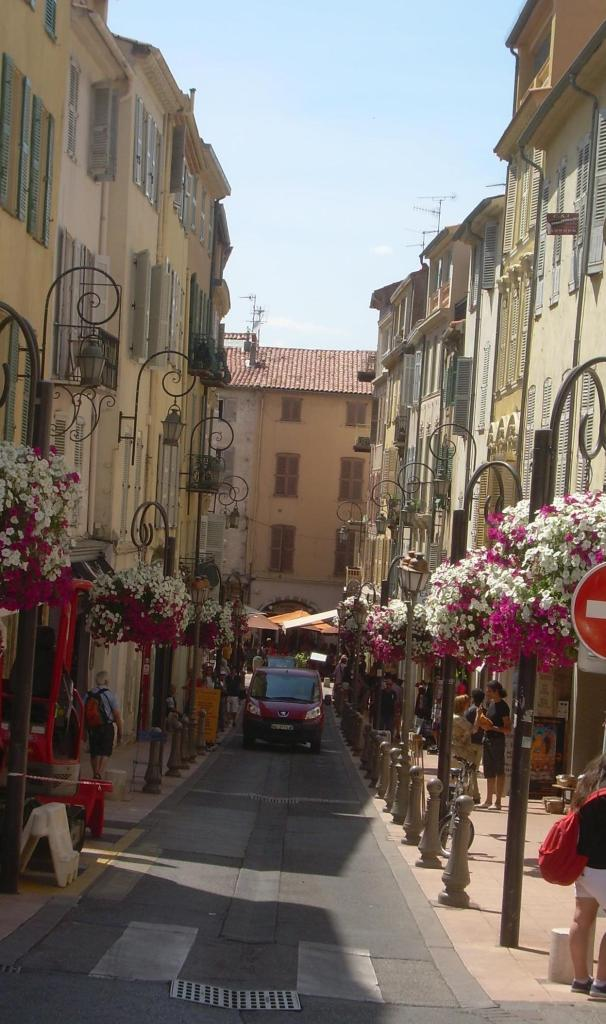 Antibes. Car driving down narrow street.