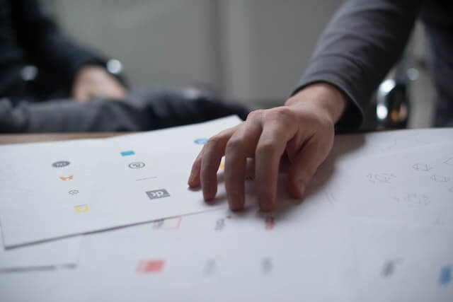 Someone's hand resting on papers with various logo designs