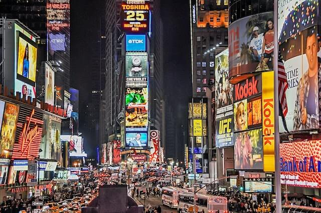 Times Square at night with various lights illuminating different brands.