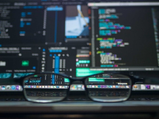 Closeup of eyeglasses on desk with computers and screen in background