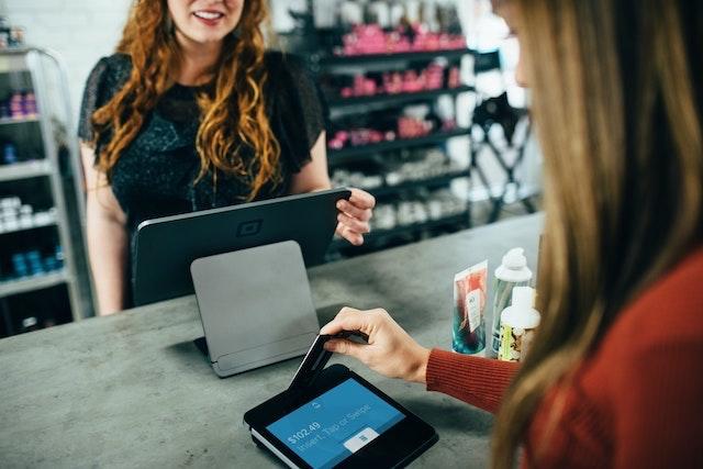 Retail worker smiling as customer slides card