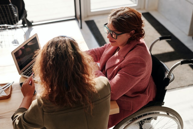 Two women chatting and looking at a laptop