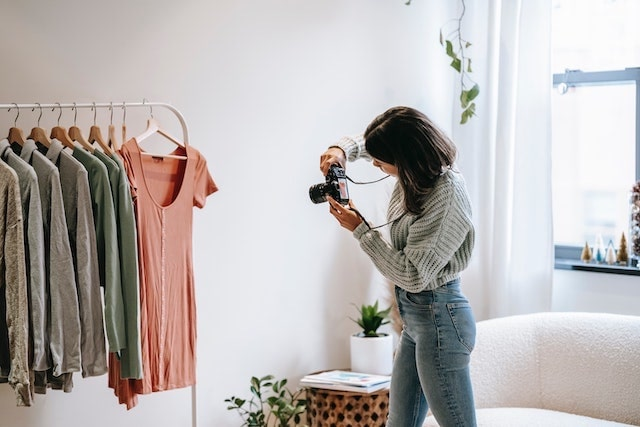 Woman taking photos of clothing using a professional camera
