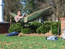 Junior marketing major Justin Rye reads a book in a hammock at the Amphitheatre. (Photo: Jamie Sapp)