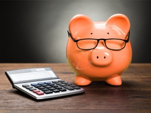 a piggy bank wears glasses and sits on a table next to a calculator