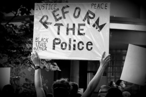 "A protester holds a sign during the June 2 BLM protest. The sign reads ""Reform the Police"""