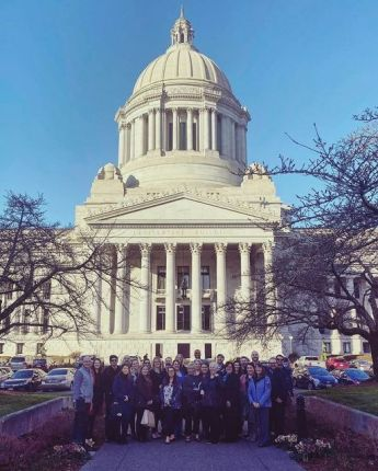 A group of individuals stand together on the sidewalk between two short walls, trees without leaves on either side. In the background a large domed building, the Washington State Capitol building in Olympia..