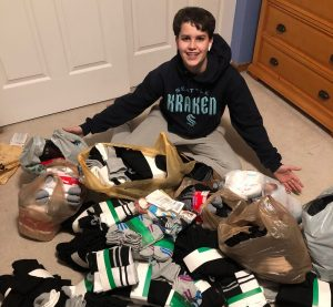 Alec Mayer, an Auburn Boy Scout, sits on the floor of a bedroom, his arms outstretched showing the large pile of black, white, and gray socks spilling out of his lap. Alec, a white teenage male with short brown hair, wears a Seattle Kraken NHL sweatshirt and gray pants.