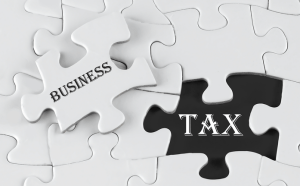 "A single puzzle piece is removed from an all white puzzle, the words ""Business"" written on it in black letters. In the place the piece was removed the word ""Tax"" is written, the space black and text white."