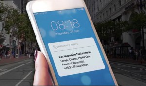 A close up of a telephone screen in a woman's hand shows an earthquake alert, instructing the person to drop, cover, hold on. and