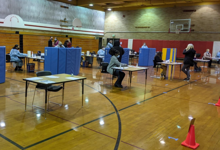 Individual testing stations (tables and chairs behind gym mats stood on end) are set up in a school gym. Individuals are throughout the gym at the stations, standing speaking, and checking in.