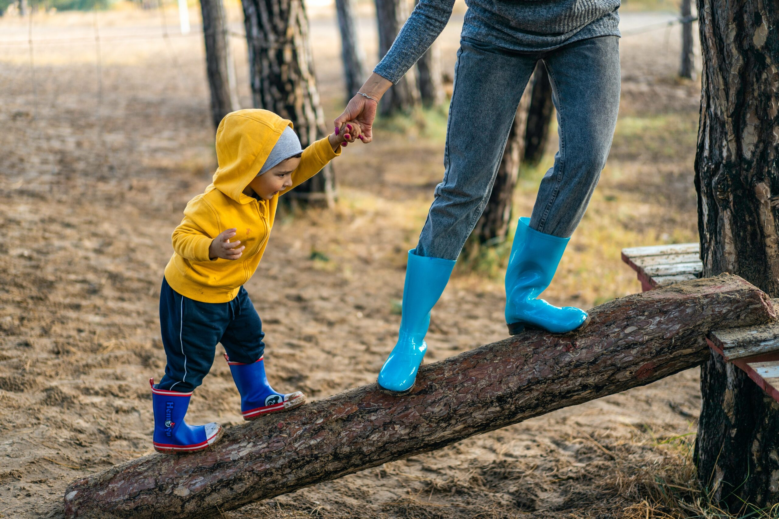 An adult and child, both wearing rubber rainboots, balance on a slanted log in the woods. The adult holds the hand of the child.