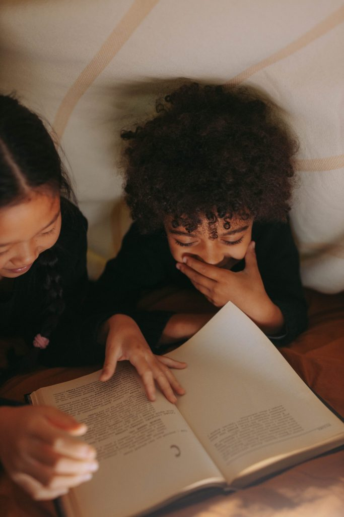 two children in bed reading a book together and giggling
