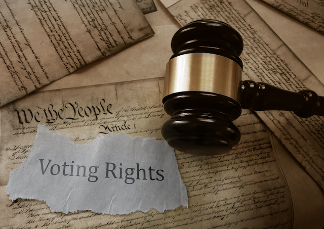 Voting Rights news headline on a copy of the US Constitution with gavel