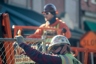 A construction worker in a hard hat and safety gear stands with his hand on top of a tall chainlink fence that surrounds a construction site. A second worker is seen in the background working.