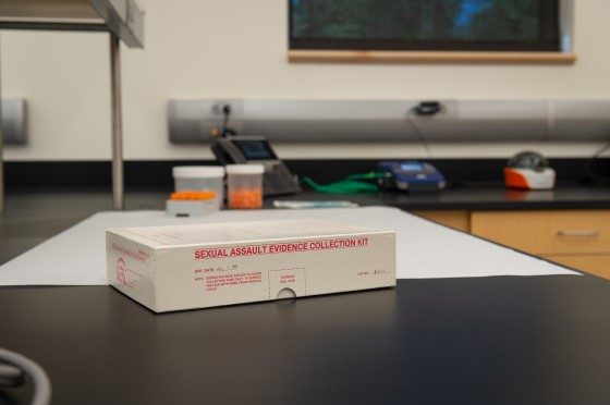 """A white box with """"Sexual Assault Kit"""" on the side sits on a black top lab table"""