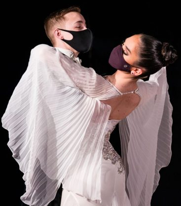 Two ballroom dancers embrace with boxed posture. The female of the pair wears a white dress with oversized bell sleeves that drape over the pair.