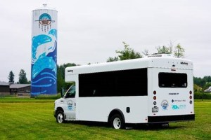 An electric bus in front of a Muckleshoot water tower.