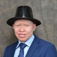 Photo of Peter Ogik with a blue jacket and tie and wearing a black hat.