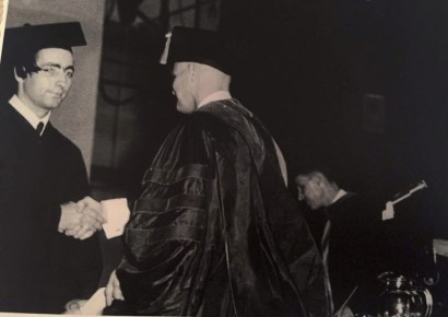 El Farouki receiving his diploma, shaking hands, in black and white