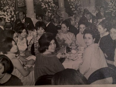a group of smiling women at a dining table, dressed up, in black and white.