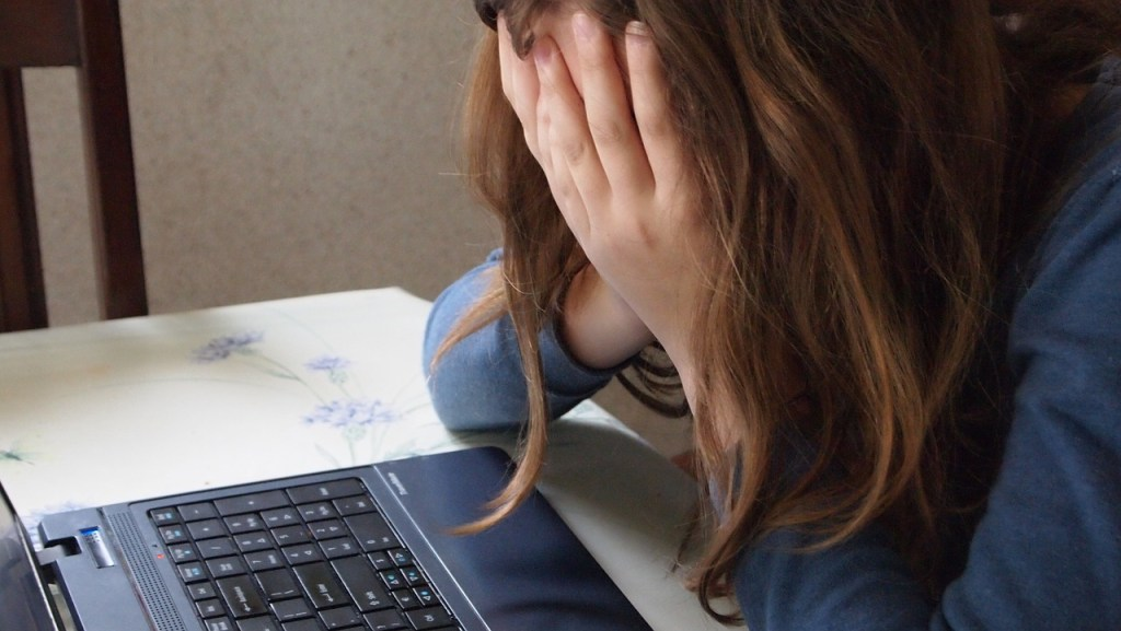Girl burying her head in her hands above a laptop