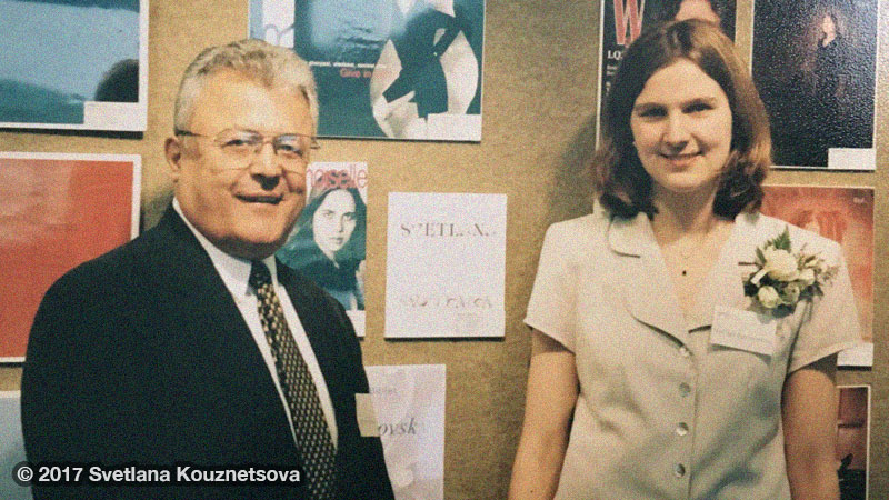 Dr. Robert Davila and Svetlana standing in front of a wall with artwork.