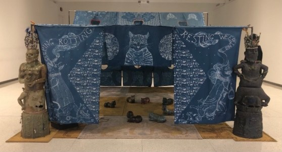 """Blue fabric draped like a tent, held up by statues of men. Two are visible. The fabric has white designs of cats on it, and the words """"sleeping, rotting, resting, weeping."""" Through the flap in the middle one can see little cat statues on the floor."""