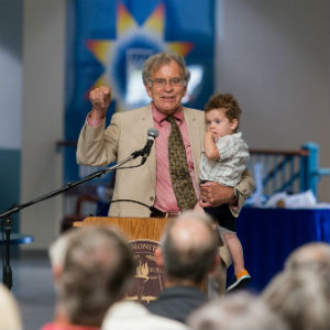 Ray Martin, class of '59, gestures while holding grandson Troy during the launch celebration for The Center for Sustainable Climate Solutions Thursday at Eastern Mennonite University. Martin's $1 million donation funded the center, which will be housed at EMU in partnership with Goshen College and Mennonite Central Committee. (Photo by Andrew Strack)