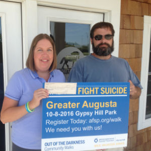 Crystal Graham, American Foundation for Suicide Prevention Virginia Chapter Secretary and co-chair of the 2016 Greater Augusta Out of the Darkness walk, accepts a $1,000 donation from Craig Nargi, owner of Hermitage Hill Farm & Stables