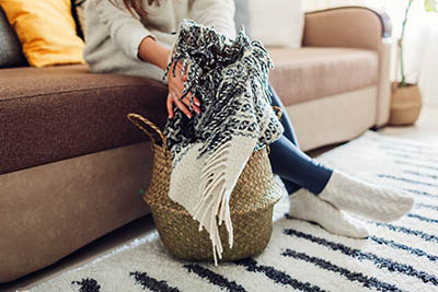 Young woman puts blanket in straw basket. Interior decor of living room