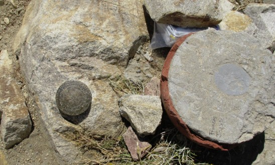 Left, US Geodetic Survey marker.. to the top right a log book in a plastic container.