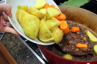 adding potatoes and carrots to pot roast