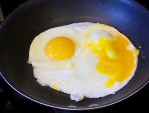 one broken egg in pan