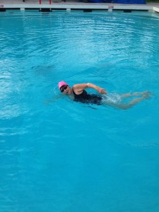 Marianna swimming front crawl in an outdoor pool.