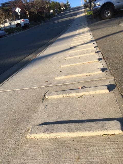 One of the most cleverest things I've ever seen! A number of sidewalks are embedded with these cement strips. It aids in climbing up the hill and it prevents one from flailing about on the way down.