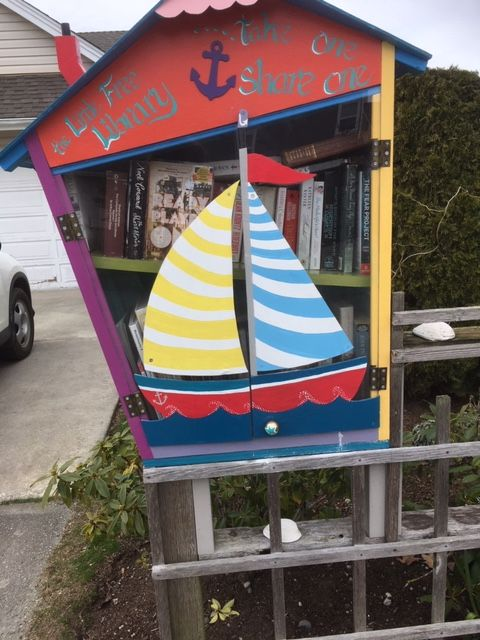 A Free Little Library with a sailboat for a door.