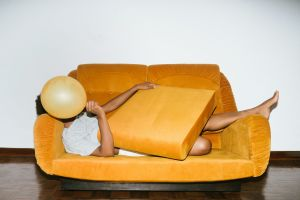 Woman stretched out, hidden, underneath a couch cushion.