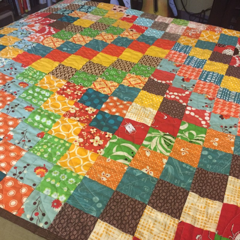 My scrappy trip along quilt that lives on my couch!.JPG