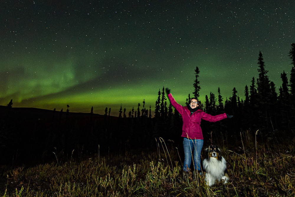 young woman dog fall aurora northern lights portrait
