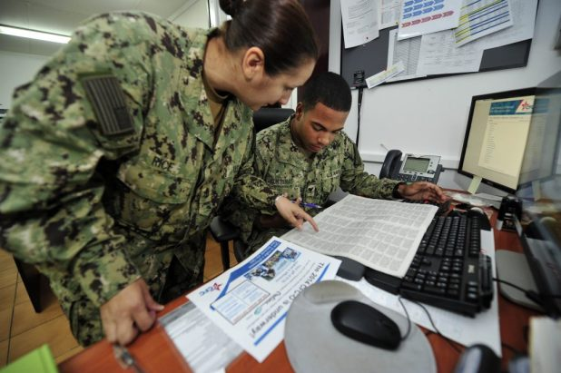 Chief Yeoman Anne Rice assists Logistics Specialist 3rd Class Jensy Contreras with paperwork.