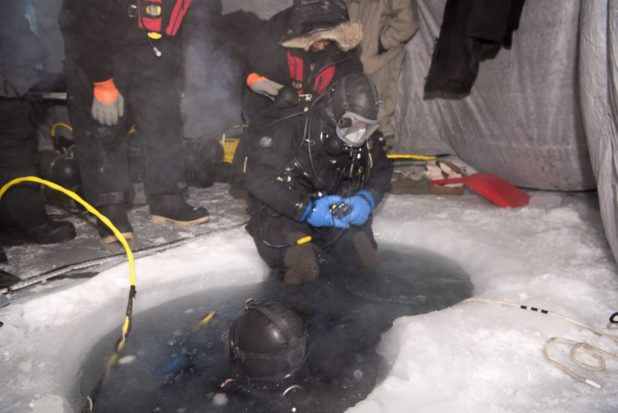BEAUFORT SEA (March 10, 2018) Navy Diver 2nd Class Christopher Corley, assigned to Underwater Construction Team (UCT) 1, prepares to dive into a water hole during a mock torpedo recovery exercise in support of Ice Exercise (ICEX) 2018. (U.S. Navy photo by Mass Communication 2nd Class Michael H. Lee/Released)