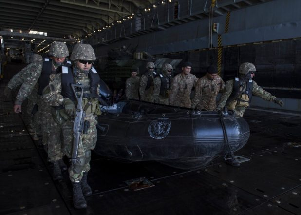 BALTIC SEA (June 8, 2018) Members of the Romanian 307th Naval Infantry Regiment carry a combat rubber raiding craft in the well deck of the Harpers Ferry-class dock landing ship USS Oak Hill (LSD 51) during a joint personnel recovery exercise as part of exercise Baltic Operations (BALTOPS) 2018. (U.S. Navy photo by Mass Communication Specialist 3rd Class Jessica L. Dowell/Released)