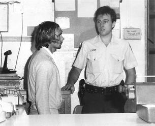 Gary Steven Murphy, 28, charged with stealing a motor vehicle, sexual assault, abduction, murder, assault and robbery of Anita Cobby, is taken into custody at Blacktown Police Station, 27 February 1986.
