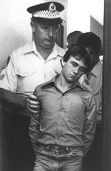 Leslie Joseph Murphy, one of five accused of the murder of Anita Cobby, is led to a waiting police van after his appearance at Westmead Coroners Court, 13 March 1986.