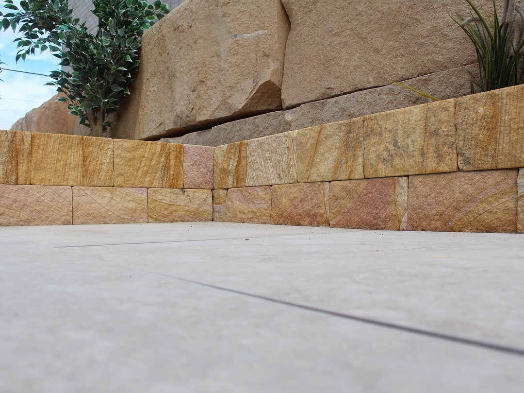 Retaining wall project using banded sandstone bricks, split sandstone block