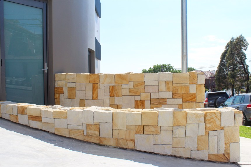 A commercial building with a stone wall using colonial banded drystone walling