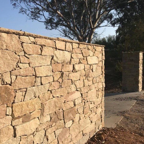 Franklin stone walling used as yard entrance wall claddings in a house design